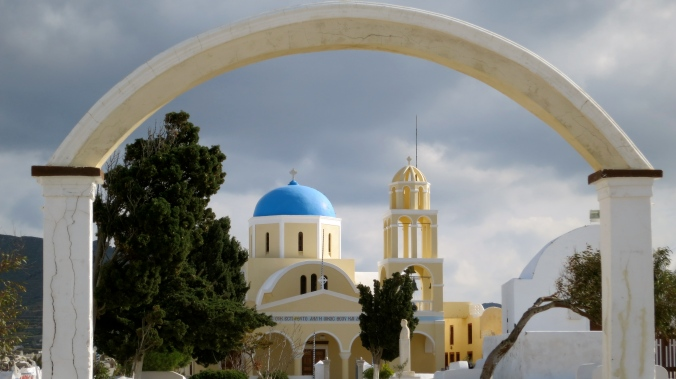 A post card type photo of a church in the town of Oia on Santorini