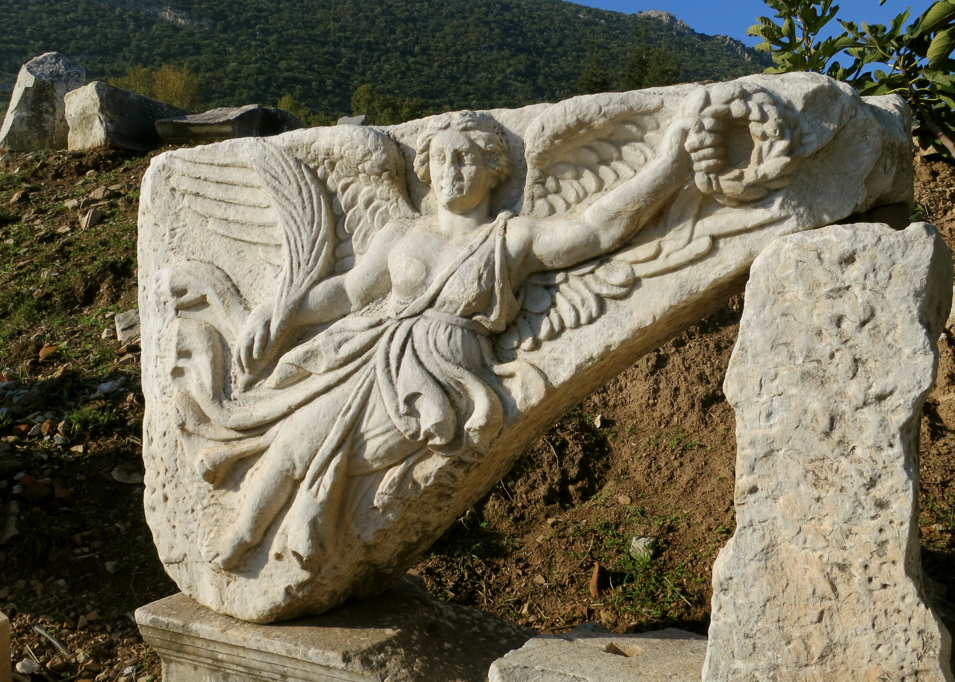 The Greek Goddess Nike, with wings all aflutter, hands over the wreath of Victory to Rome... which is appropriate since Rome took over the Greek city and turned it into the second largest city in the Roman Empire.