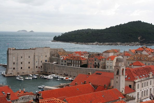 A view looking down on Dubrovnik's port and St. John's fortress that guarded the  harbor against Venetian invasion during the Middle Ages. The towns clock tower is on the right. (Photo by Peggy Mekemson)