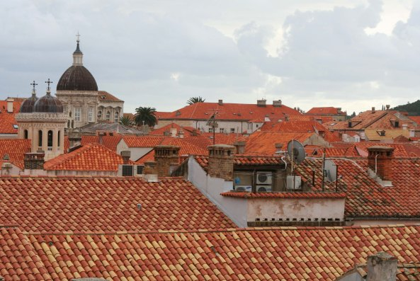 This view of red tile roofs and cloudy skies features Dubrovnik's Cathedral on the left.