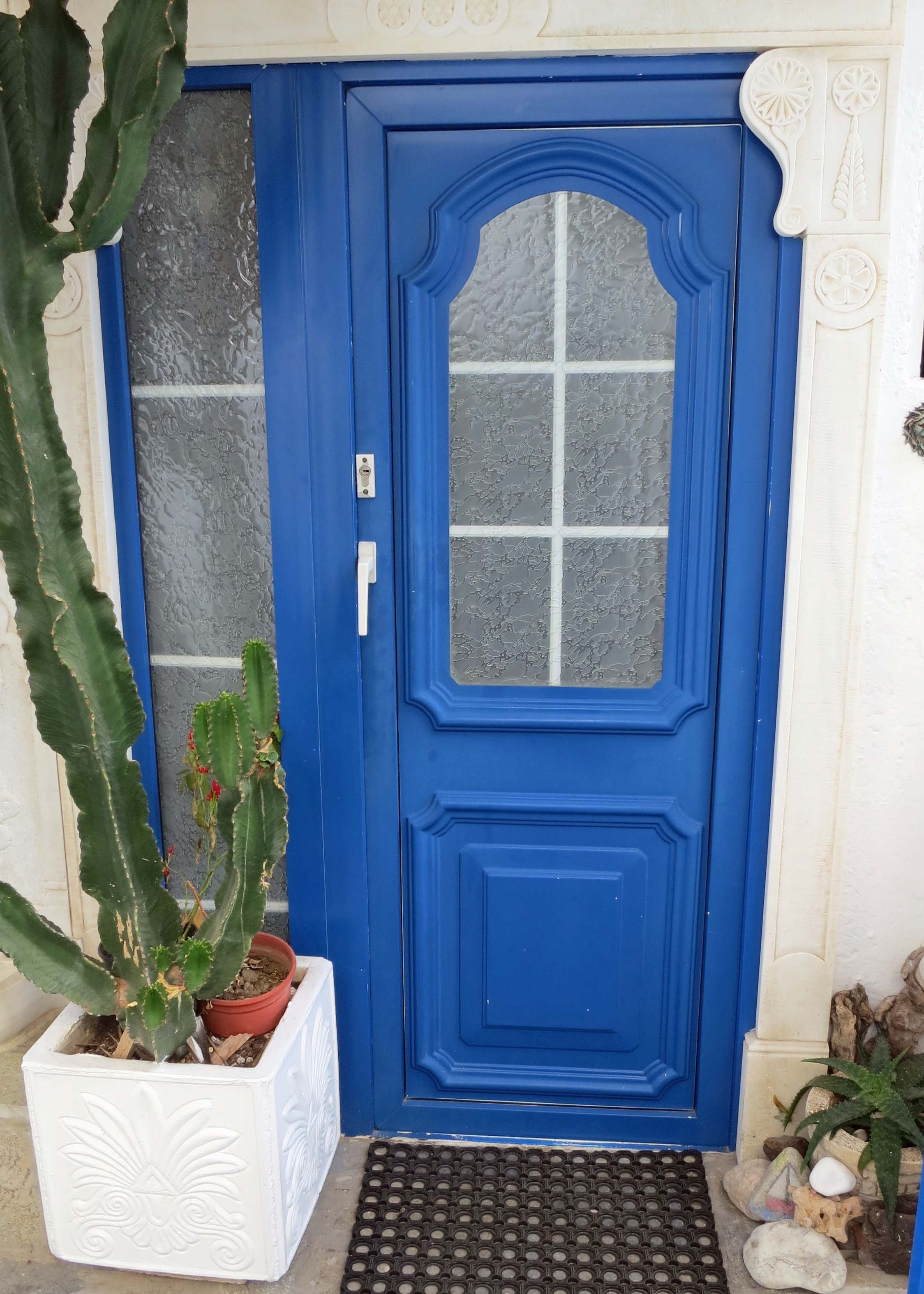This blue Mykonos door is decorated by a cactus.