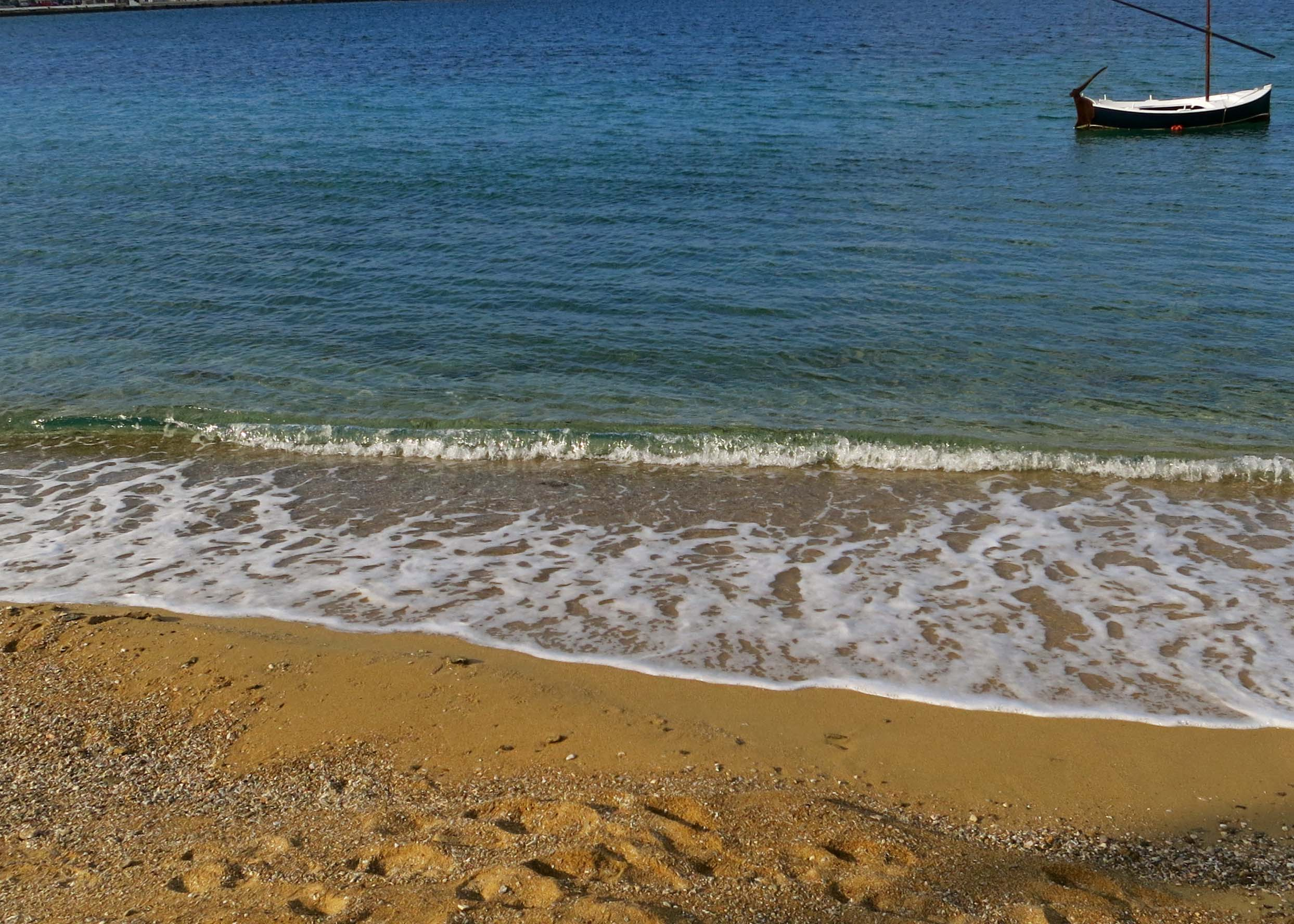 The golden sands and blue waters of the Aegean Sea of the small beach in Mykonos.