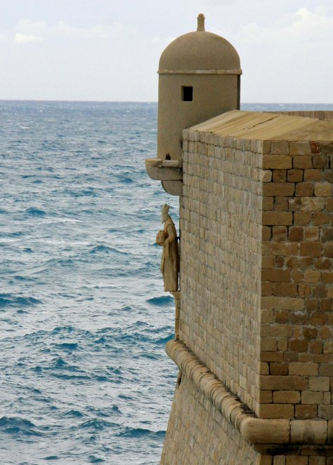 A statue of St. Blaise, the Patron Saint of Dubrovnik, looks out on the Adriatic Sea under a watch tower protecting the city from harm. (Photo by Peggy Mekemson)