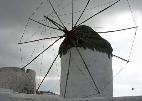 "One of the windmills of Mykonos. Dark clouds brought brief rain and a ""throw a chair"" wind."