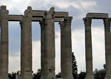 A side view of the Temple of Zeus in Athens looking grey against grey skies.