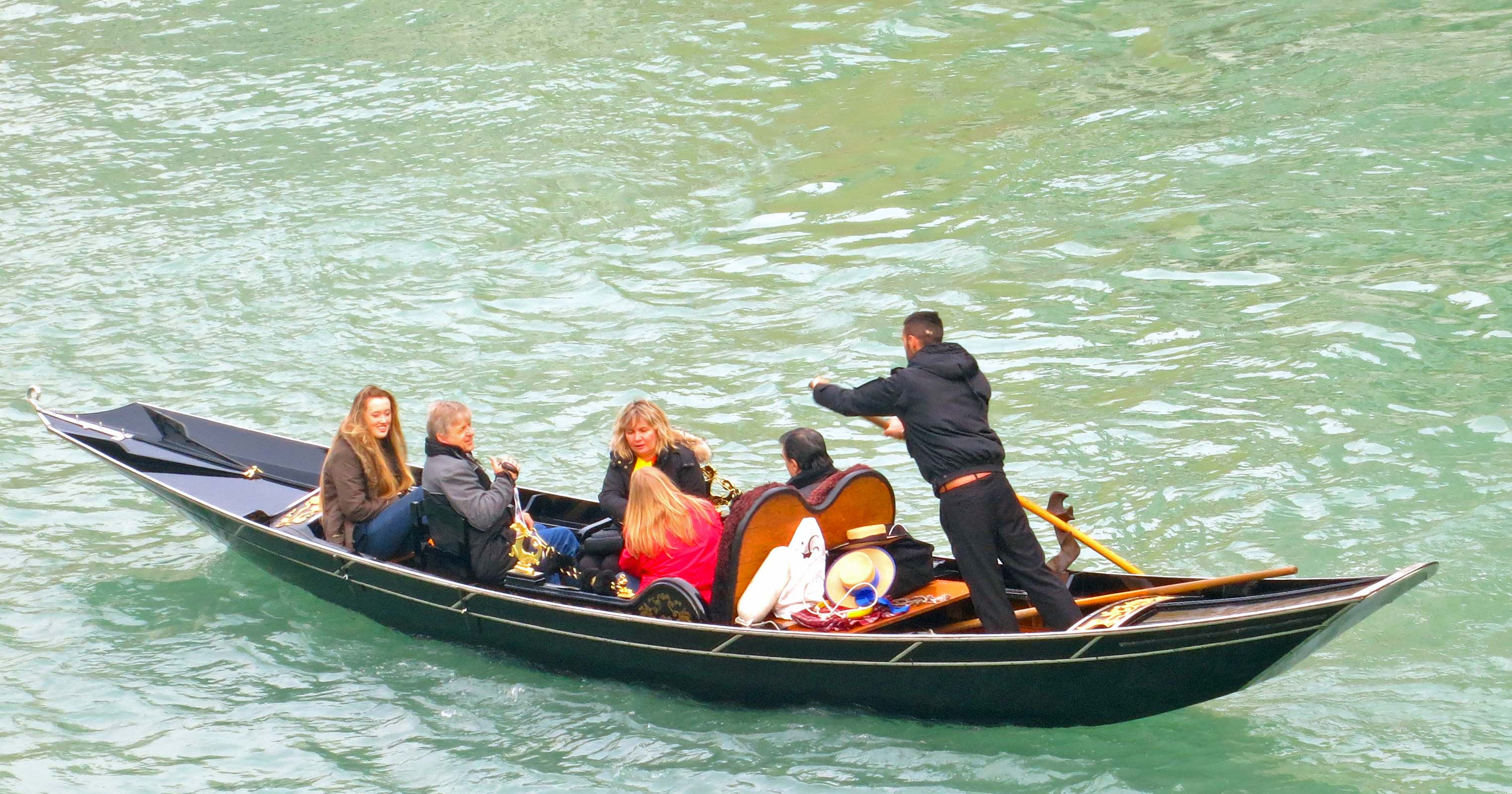 A gondolier works his boat on cold, rough waters in the Grand Canal as his passengers enjoy the ride, bundled up in warm clothes.