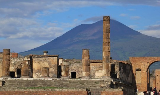 Mt. Vesuvius rises above the Temple of Jupiter in Pompeii.