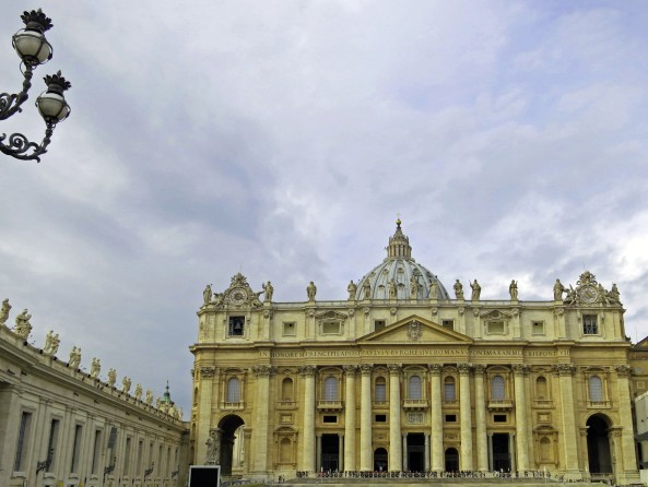Cloudy skies provide a dramatic backdrop for St. Peter's Basilica with its magnificent dome designed by Michelangelo.