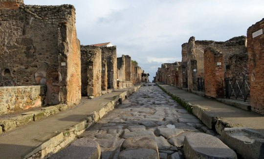 A typical Pompeii street scene featuring stepping stones, sidewalks, and shops. It amazed me how well the city was laid out.