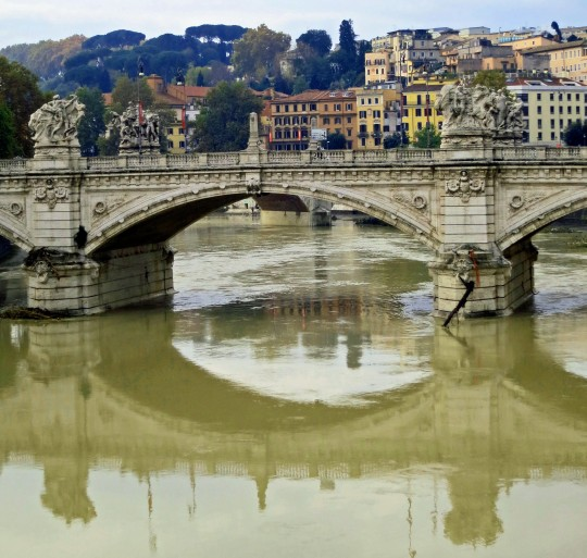 The Victor Immanuel Bridge reflected in the Tiber River of Rome.