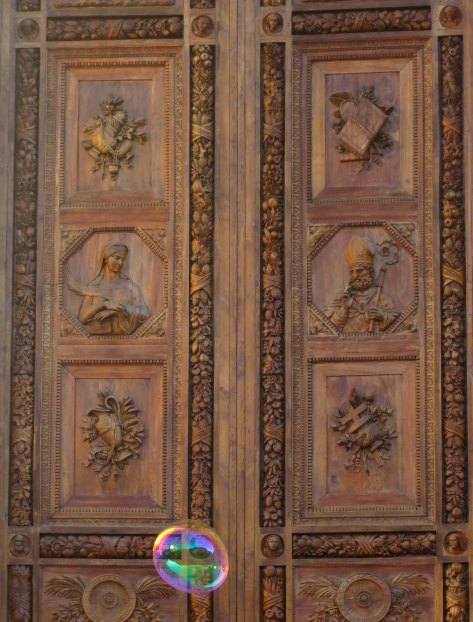 A huge soap bubble went floating up by the beautiful wooden doors of Santa Croce.