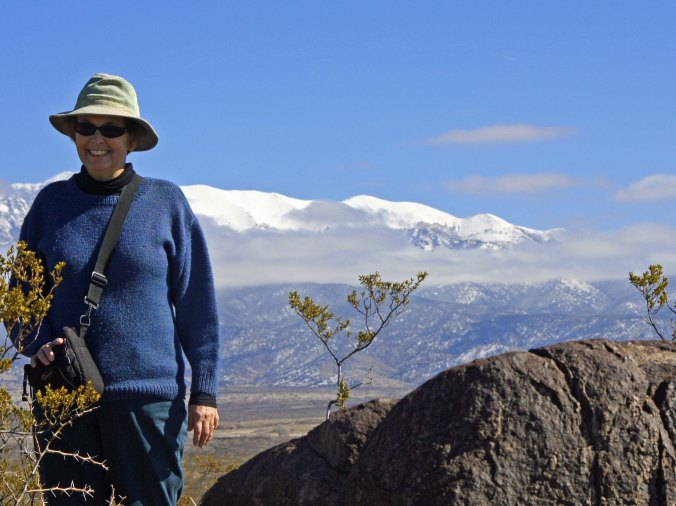 Peggy stands on the ridge next to a rock likely to hold petroglyphs. Some glyphs are immediately obvious while others are hidden. Sharp eyes are required.