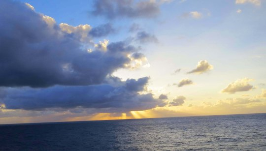 Sun shining through clouds on the Atlantic Ocean.