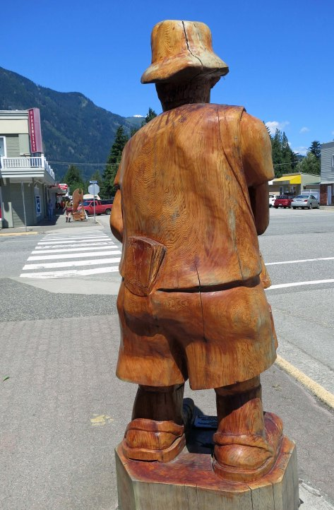 Many of the chainsaw woodcarvings in Hope, BC display a sense of humor such as this tourist with a guidebook in his hip pocket.