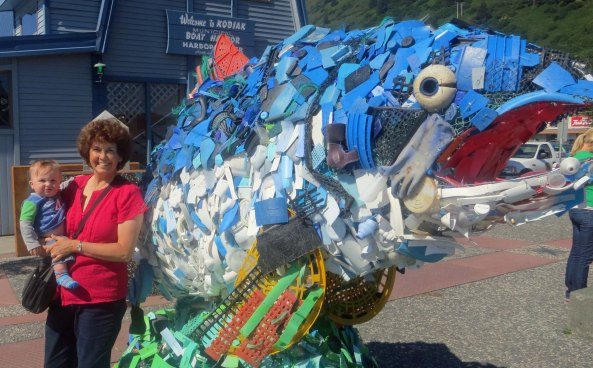 Peggy poses with out youngest grandson, Cooper in front of the Harbor Masters office in Kodiak. The large fish is a sculpture made from trash collected from the ocean. Hopefully Cooper will grow up in a world with less trash.