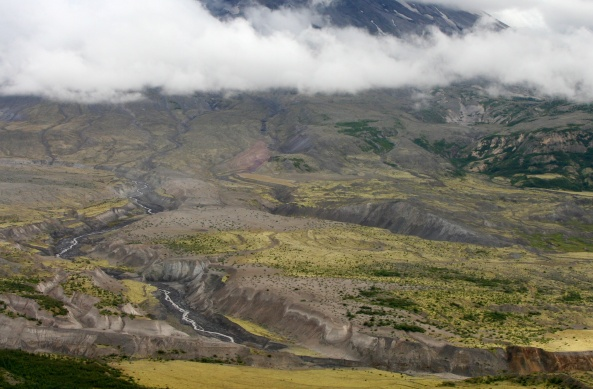 Looking down at the valley floor in front of Mt. St. Helen, the Toutle River carves through debris left behind by the eruption which reaches a depth of over 300 feet in places.