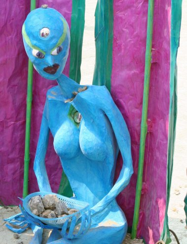 Blue alien woman at Burning Man 2013 with fine collection of rocks.