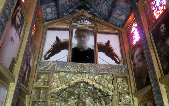 """A view from inside the Photo Chapel. The person featured is Joey Jello, a member of Black Rock City's Department of Public Works who die in an auto crash just before 2012 Burning Man. His motto, shown below, was """"Never Betray."""" It referred to his core values."""