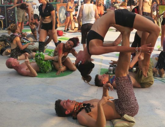 A show of some kind of the other is pretty much guaranteed when you visit the Center Camp Cafe. Here couples practice partner yoga. Are the two guys center-right twins?