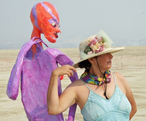Peggy Mekemson dances with alien at Burning Man 2013.