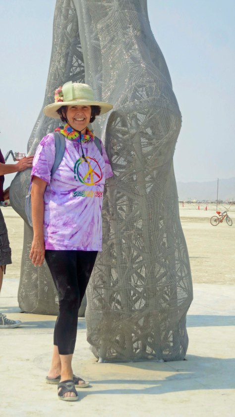 Peggy Mekemson standing in front of sculpture Truth Is Beauty at Burning Man 2013.