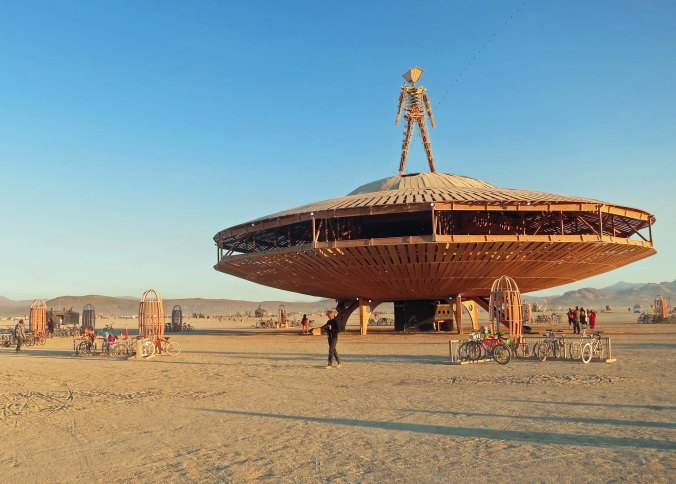 The Man of Burning Man 2013 perches on a flying saucer and overlooks Black Rock City with its 68,000 participants.