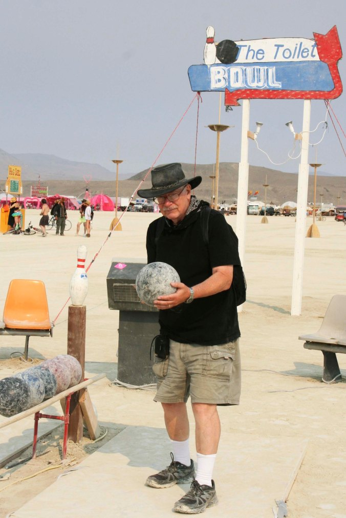 Colorful signs announced the presence of some port-a-potties on the Playa. This one was named the Toilet Bowl and came with a bowling alley. Here I line up to take a shot. I managed to knock down all but one pin. (photo by Peggy Mekemson)