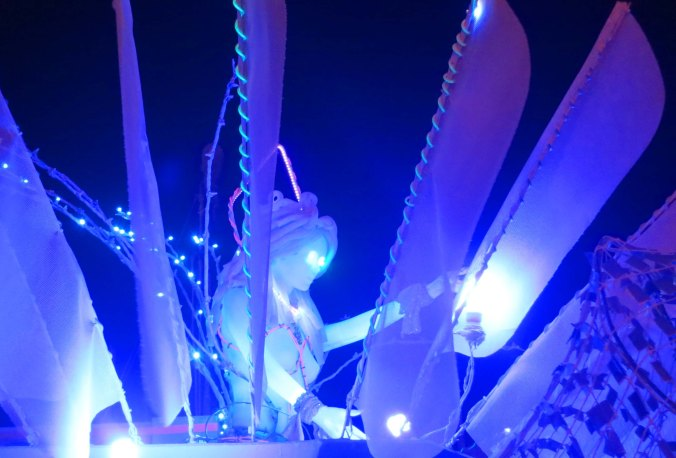 Mutant vehicle features blue lady with flashing eyes at Burning Man 2013.
