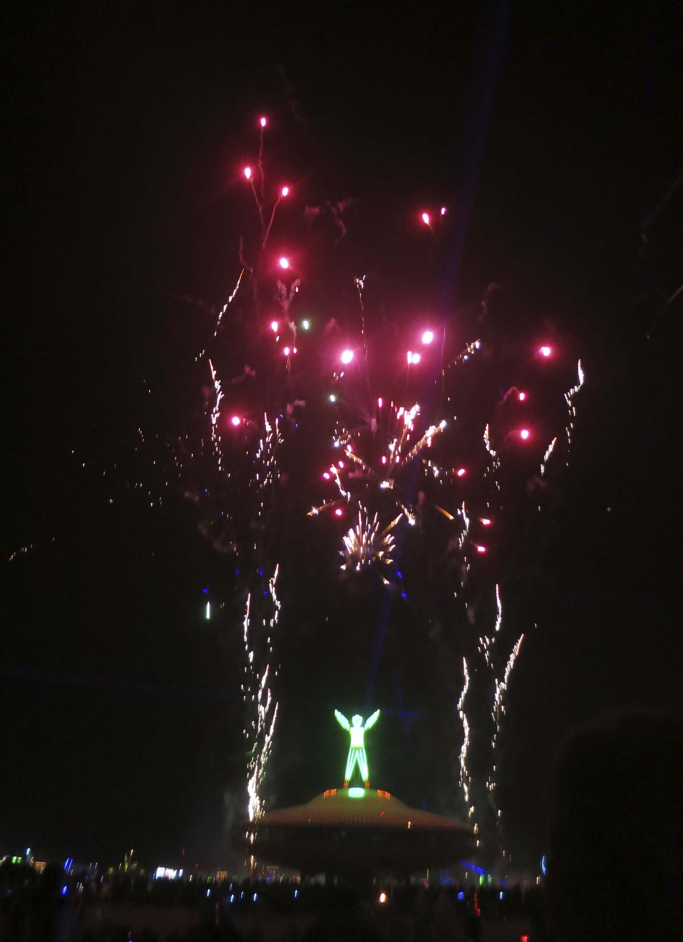 Man outlined by fireworks at Burning Man 2013.
