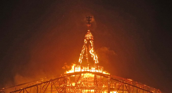A few remaining timbers hold up the Man at Burning Man 2013 before he crashes into his fiery grave.