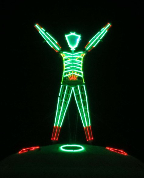The Man at Burning Man raises his arms just prior to the burn.