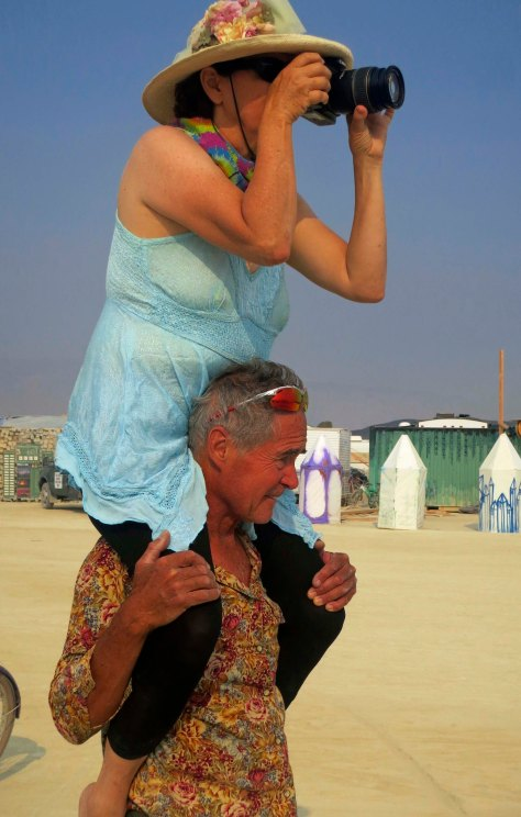 A photo op of a photo op. Tom needed a photo and somehow decided that Peggy resting on his shoulders was better than me resting on his shoulders. I wonder why?  Anyway, 60,000 people at Burning Man pretty much guarantees 60,000 cameras. Let's assume for the moment that each person takes an average of 100 photos, which is a conservative estimate in today's world of digital cameras.  That means a conservative 6 million photos were taken at Burning Man 2013.