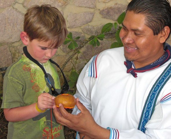 Ernesto shows lets our grandson Cody press beads onto a gourd covered with beeswax. (Photo by Ethan's mom, Natasha.)