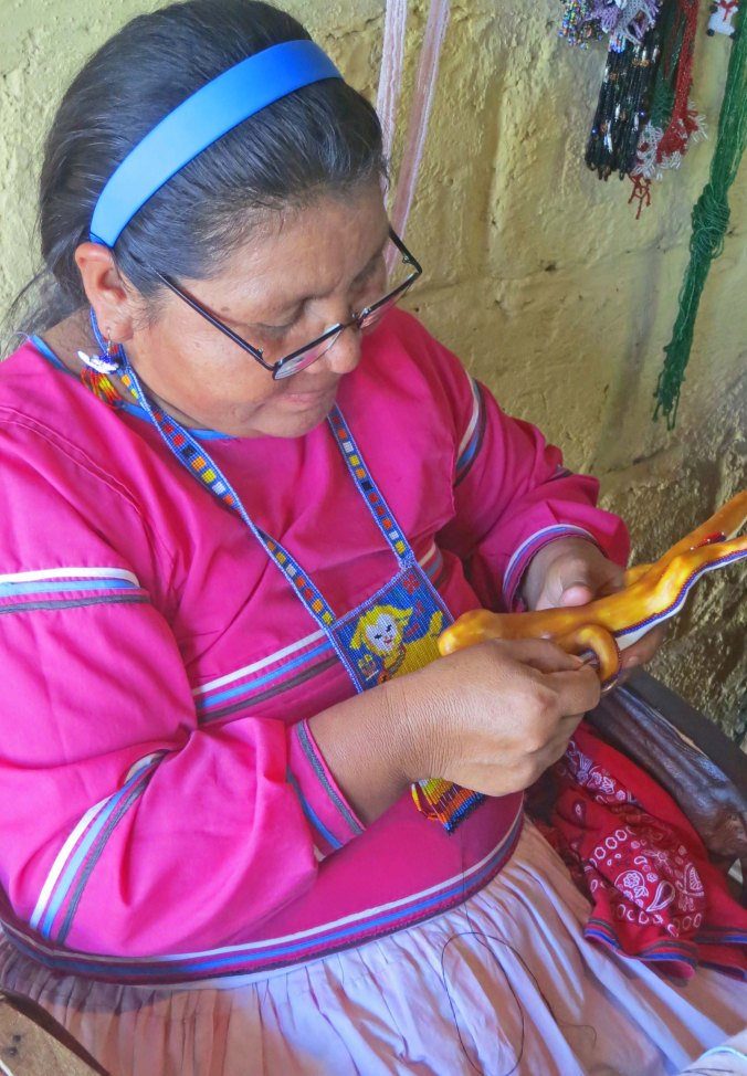 Huichol woman works on a bead art sculpture in Mexico. Photo by Curtis Mekemson.
