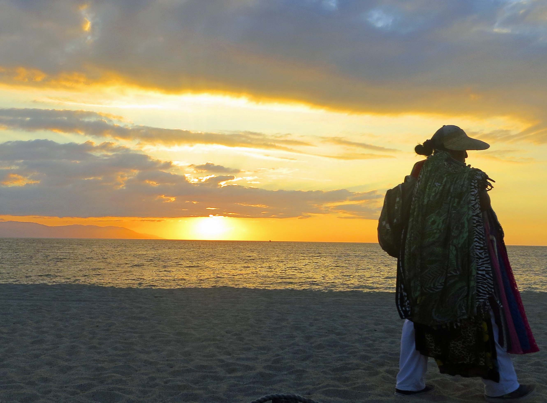 Puerto Vallarta beach vendor outlined by setting sun. Photo by Curtis Mekemson.)