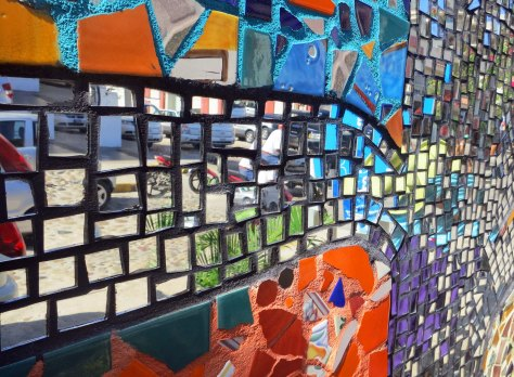 Made with tile and glass, the mural uses mirrors to reflect the street scene behind it, an effort that adds both beauty and interest.