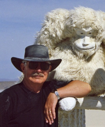 I made my first journey to Burning Man in 2003. This photo is taken from 2006 when I posed next to a great ape in an evolution sculpture. Playa dust decorates my hat and T-shirt.