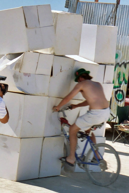 Cyclist knocks down boxes at Burning Man.