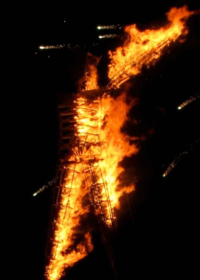 The Man burns at Burning Man while fireworks shoot across the sky.