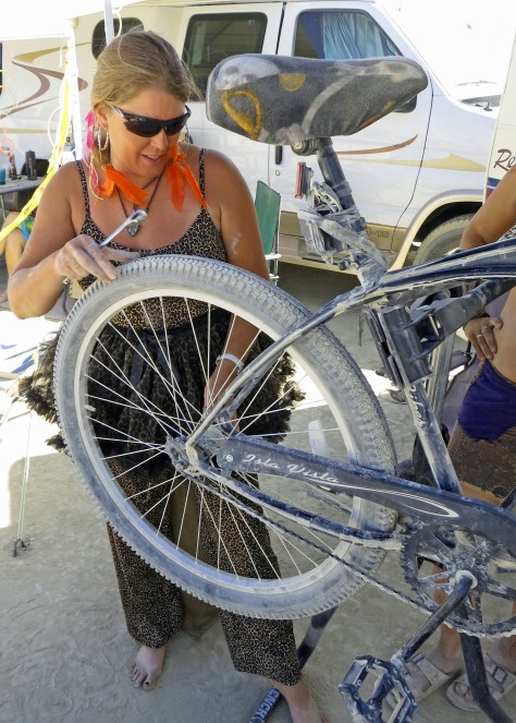Fixing bikes is another important form of gifting at Burning Man. Beth is a master mechanic who owns a bike shop in Davis. My van Quivera provides the backdrop for the photo.
