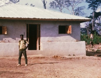 Mamadee standing in front of his house. Later Mamadee would become an elementary school principal in New Jersey.