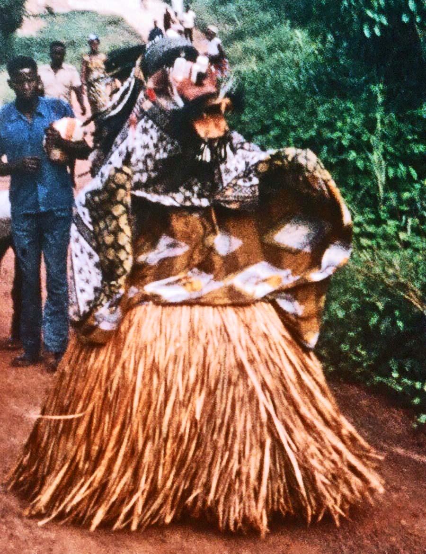 Pat hay stack and part voodoo nightmare, a Liberian Bush Devil shuffles through the dirt toward me.