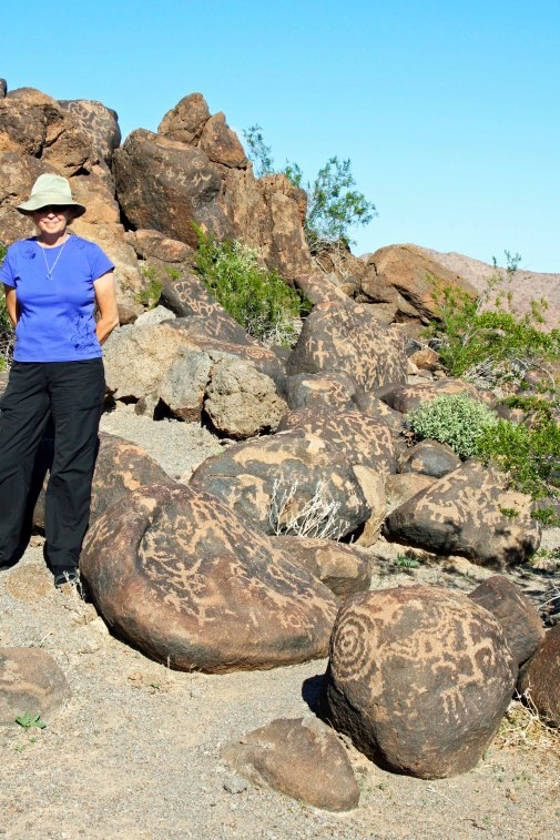 The rocks at Painted Rock Petroglyph Site in Southern Arizona are covered with petroglyphs as shown in this photo with Peggy.