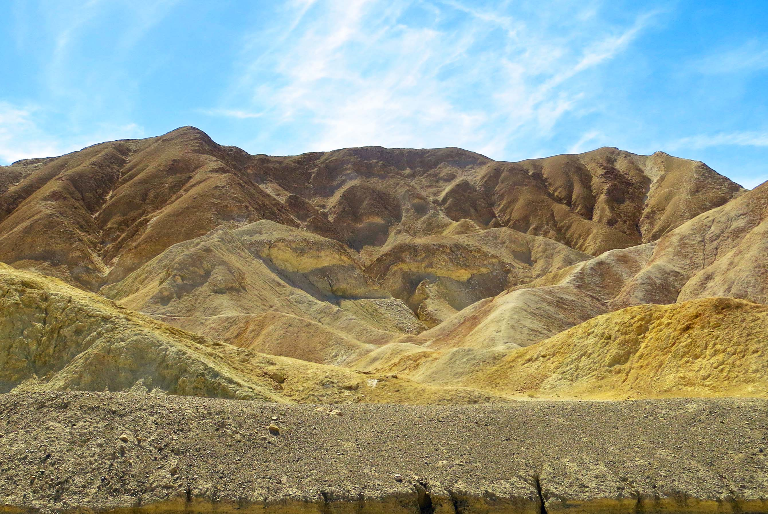 Photo of blue skies with puffy clouds provides backdrop for Twenty Mule Team Canyon in Death Valley.