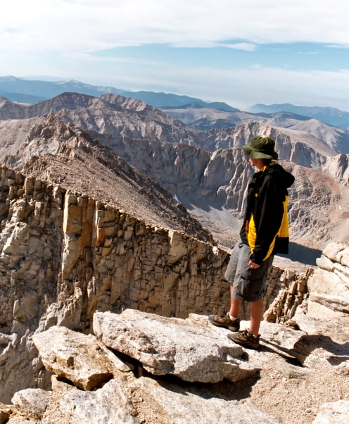 Jay Dallen standing on the edge of Mt. Whitney.