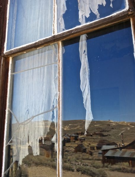 Tattered curtains, a cracked window, and a reflection of weather warn buildings capture the essence of the Old West ghost town of Bodie, California.
