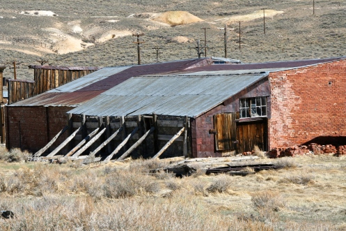 Building held up by support beams at Bodie State Park in California.