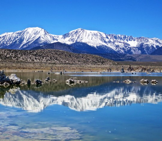 The Sierra Nevada Mountains provide a scenic backdrop in the west for Mono Lake. Highway 395 runs slog the base of the foothills. Tufa can be seen emerging from the lake.