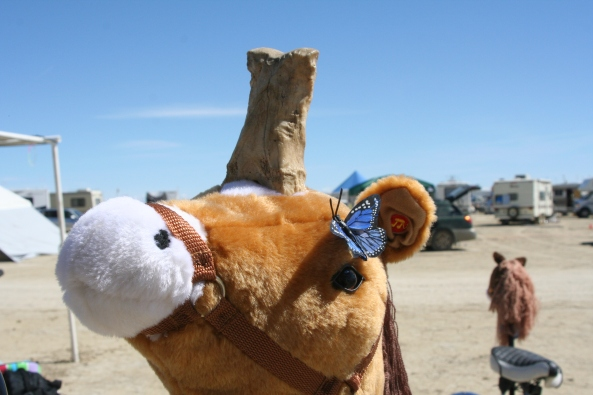Bone hitches a ride on a willing horse at Burning Man.