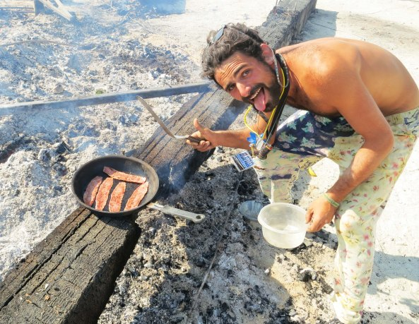 Cooking bacon on the coals left over from the burning of the man at Burning Man 2014.